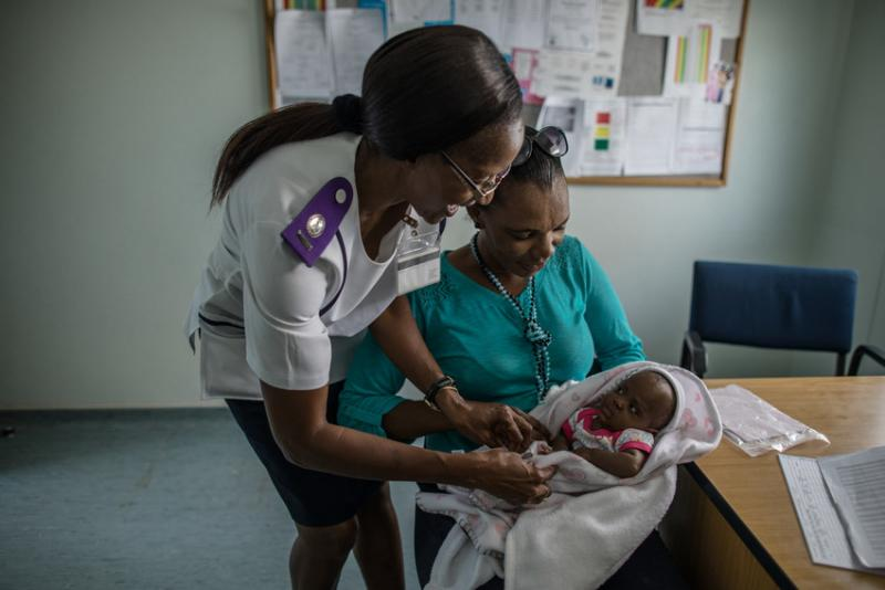 Nurse Ruusa Shipena (left) consults with an HIV-positive mother after the birth of her HIV-negative baby at Shanamutango HIV clinic, Onandjokwe Hopsital, Namibia. Photo by Morgana Wingard for IntraHealth International.