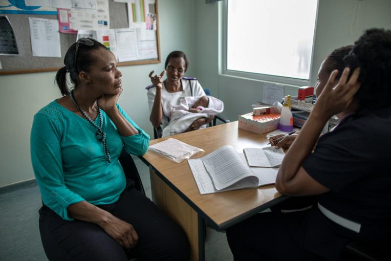"""""""We were short on the ground, especially when it came to nurses and admin staff,"""" says nurse Ruusa Shipena (center). """"Then IntraHealth came in and gave us more staff. Now some can draw blood, while some can do counseling, while some do pediatrics. And now we can do outreach, and perform services outside the center, not only inside the center. To us, it's our rescue."""" Photo by Morgana Wingard for IntraHealth International."""