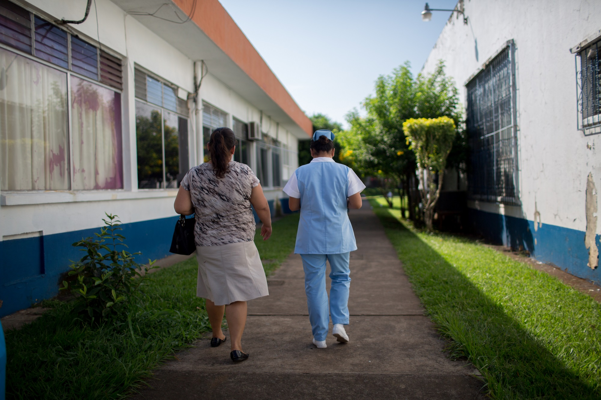 A nurse takes escorts a client to health services in Guatemala. Photo by Anna Watts for IntraHealth International.
